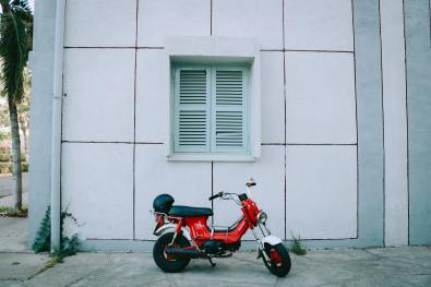 red-motor-scooter-parked-beside-white-concrete-building-2044876
